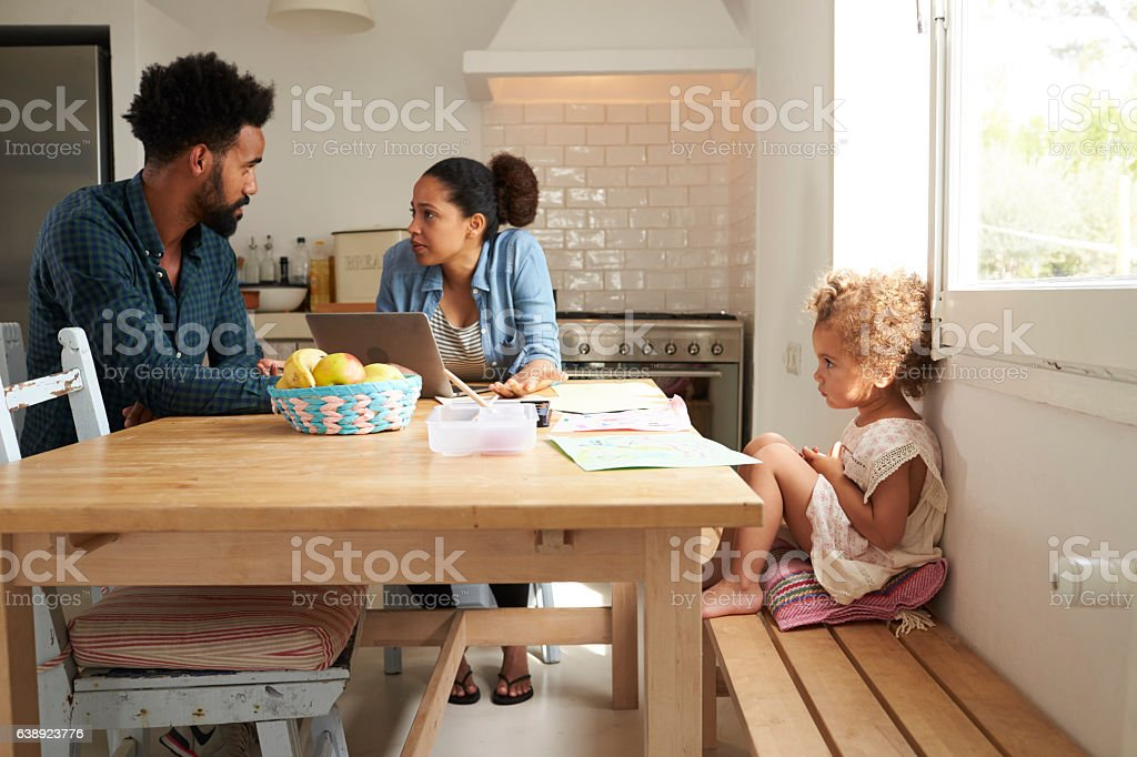 Unhappy Girl Watching Parents Arguing In Kitchen stock photo