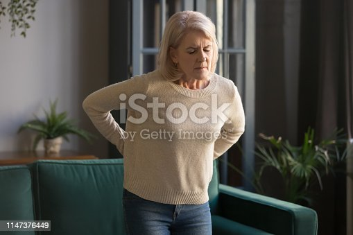 821012164istockphoto Unhappy grey haired mature woman touching back, suffering from backache 1147376449