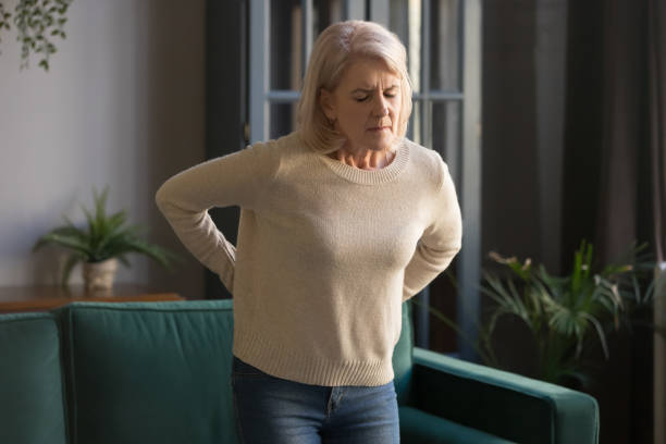 unhappy grey haired mature woman touching back, suffering from backache - midsection stock pictures, royalty-free photos & images