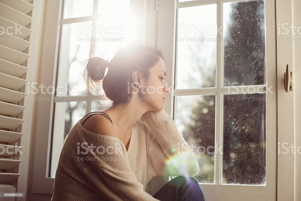 Unhappy housewife sitting near the window - Lizenzfrei Abgeschiedenheit Stock-Foto