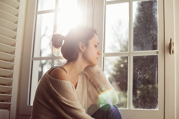 Unhappy housewife sitting near the window stock photo