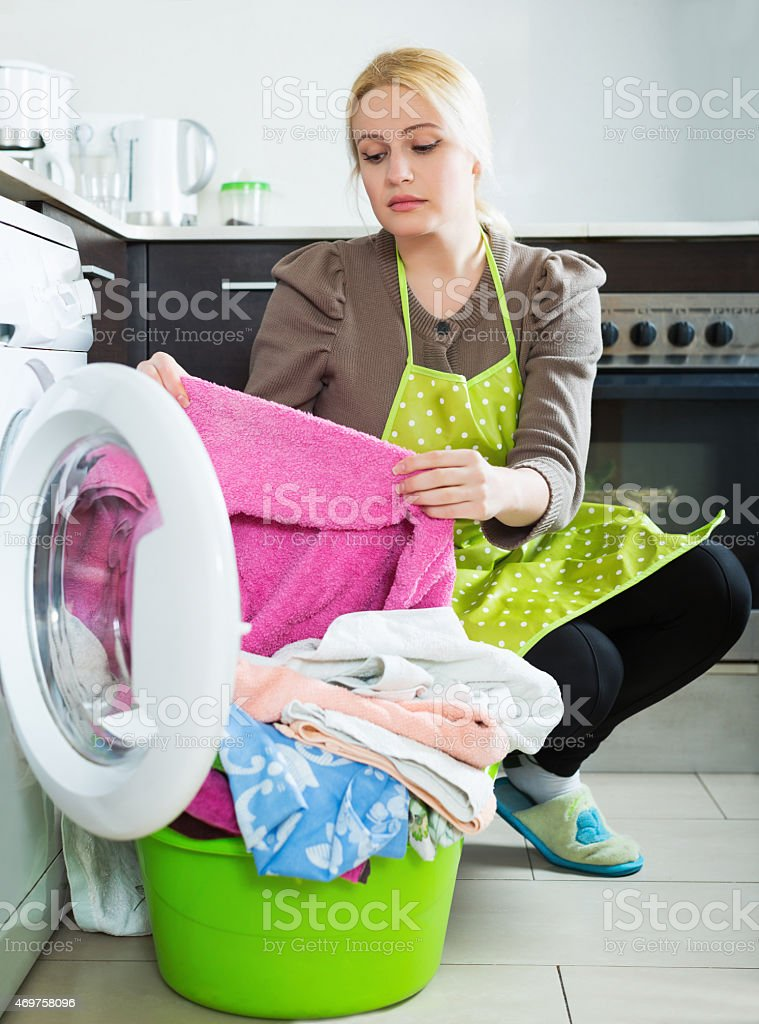 Unhappy housewife with clothes stock photo