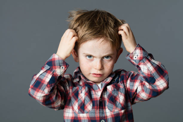 unhappy kid scratching his hair for head lice or allergies - tête humaine photos et images de collection