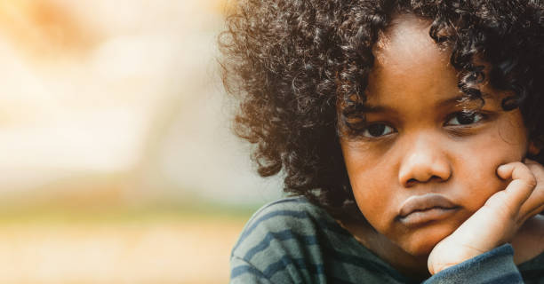Unhappy little african american kid in the park. stock photo