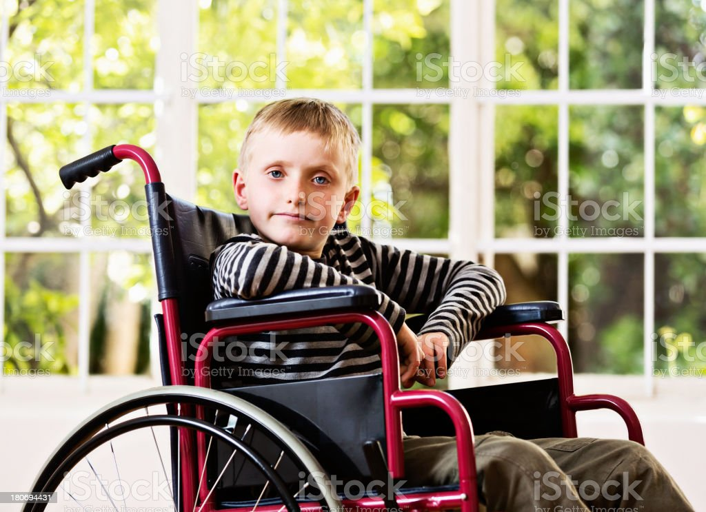 Unhappy little boy confined to wheelchair resents his situation stock photo