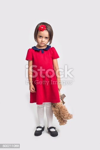 istock Unhappy little girl in a red dress with toy bear 500211088