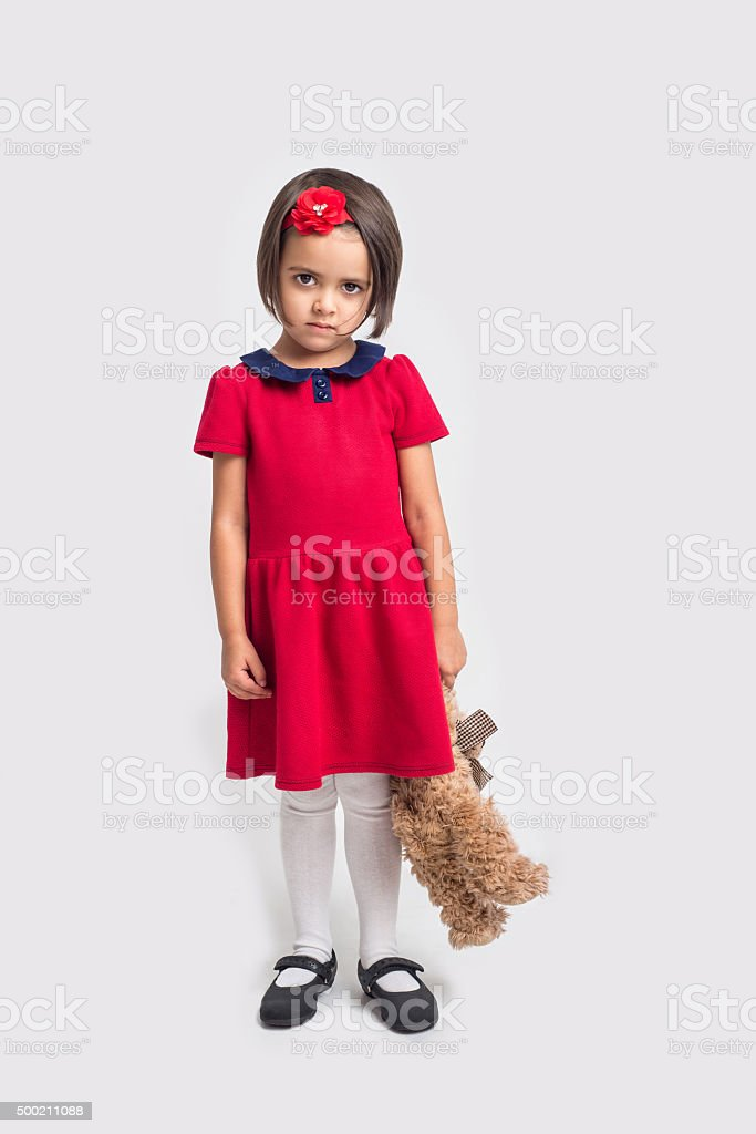 Unhappy little girl in a red dress with toy bear stock photo