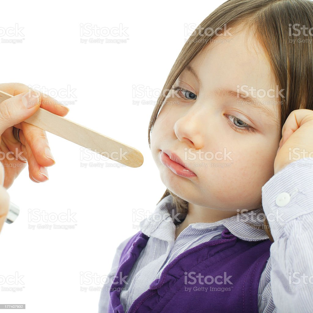 Unhappy little girl with tongue depressor royalty-free stock photo