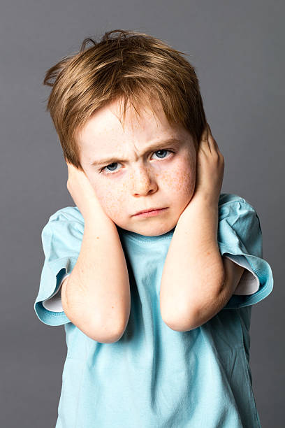 unhappy little kid disliking his education, protecting his closed ears unhappy little kid disliking his education, protecting his closed ears with both hands, ignoring his parents scolding, grey background hands covering ears stock pictures, royalty-free photos & images