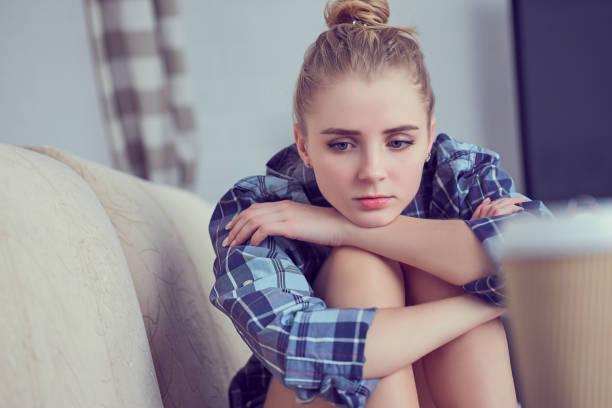 Teenager-Mädchen zu Hause unglücklich einsam depressiv, sie sitzt auf der Couch und stützte ihren Kopf mit seinen Füßen. Depression der Jugend-Konzept – Foto
