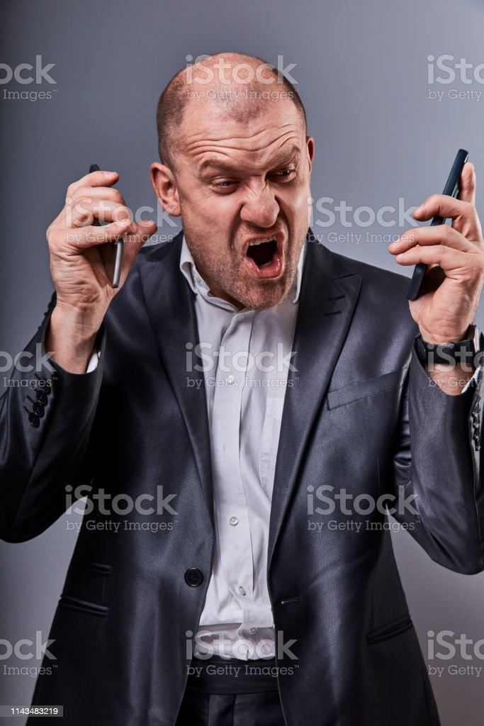Unhappy loud crying anger business man talking on two mobile phones very emotional in office suit on grey studio background. Closeup royalty-free stock photo