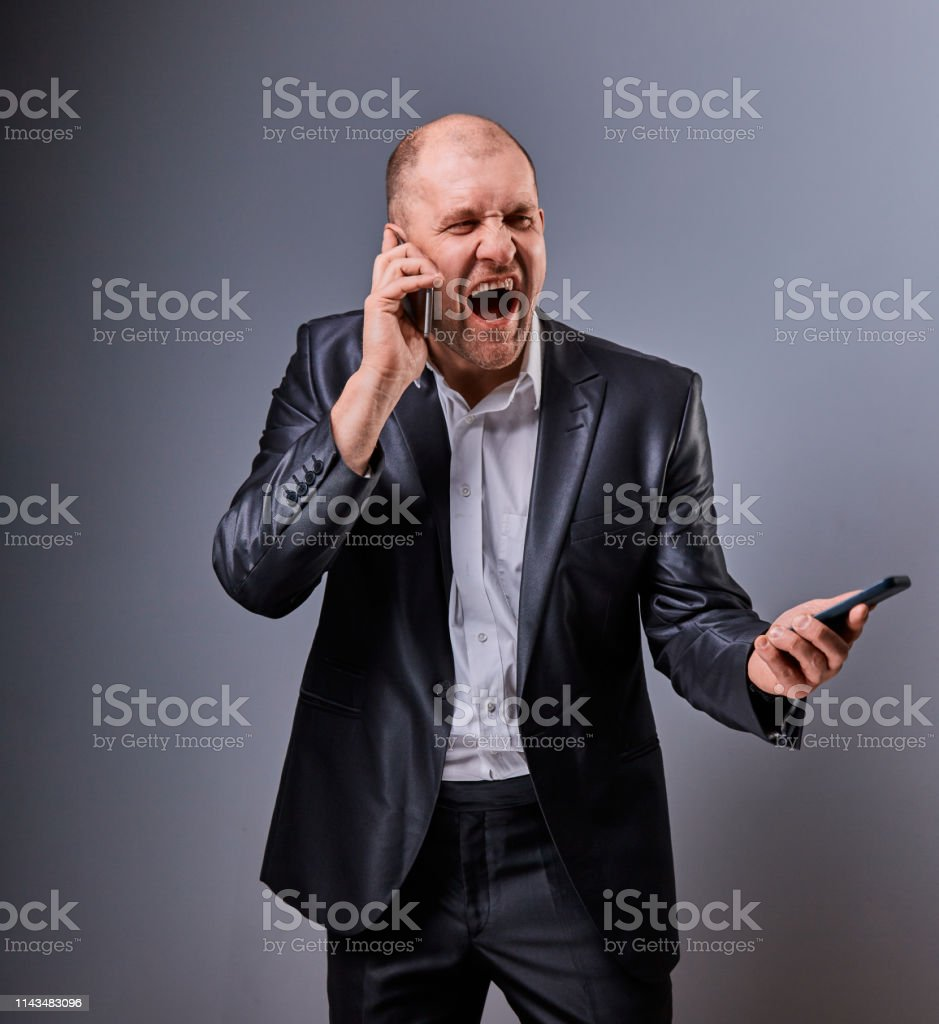 Unhappy loud crying angry business man talking on mobile phone very emotional in office suit on grey background. Closeup royalty-free stock photo