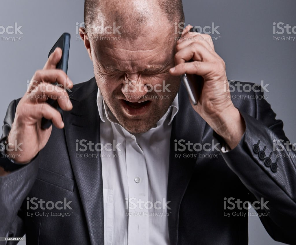 Unhappy loud crying angry business man talking on mobile phone very horrible emotions in office suit on grey studio background. Closeup contrast royalty-free stock photo