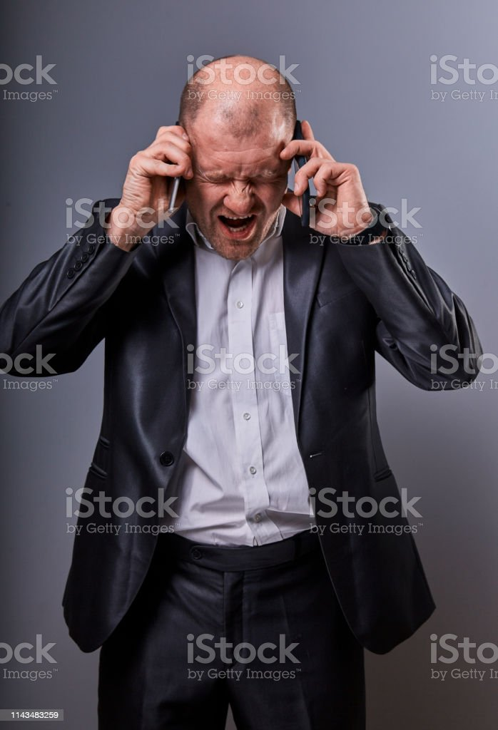 Unhappy loud crying angry business man talking on mobile phone very emotional wide opened mouth in office suit on grey background. Closeup royalty-free stock photo