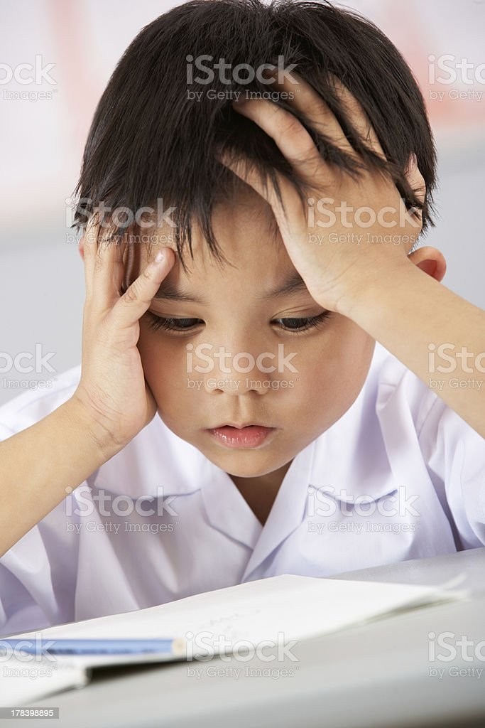 Unhappy Male Student Working At Desk In Chinese School Classroom stock photo