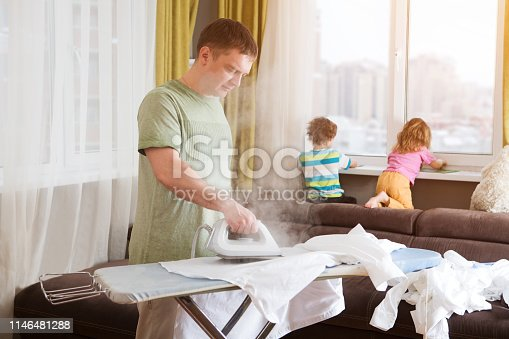 Unhappy man at home ironing clothes  in laundry room at home. Man doing housework and children
