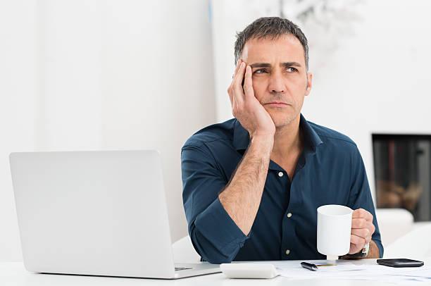 unhappy man at the desk - mid volwassen mannen stockfoto's en -beelden