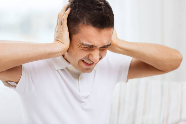 unhappy man closing his ears by hands at home people, crisis, emotions, noise and stress concept - unhappy man closing his ears by hands at home hear no evil stock pictures, royalty-free photos & images