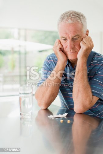 istock Unhappy man looking at pills on counter 107429880