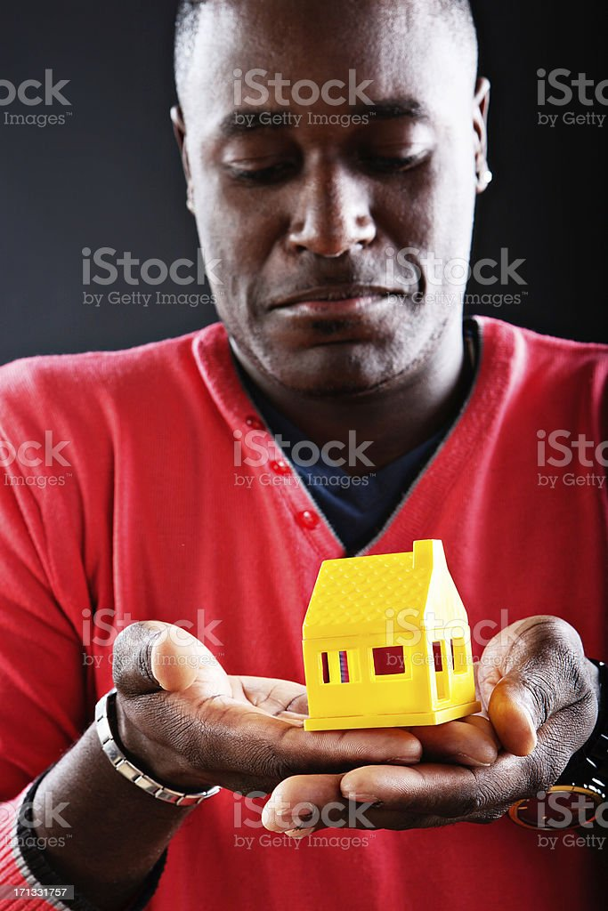 Unhappy man looks down at yellow toy house frowning stock photo