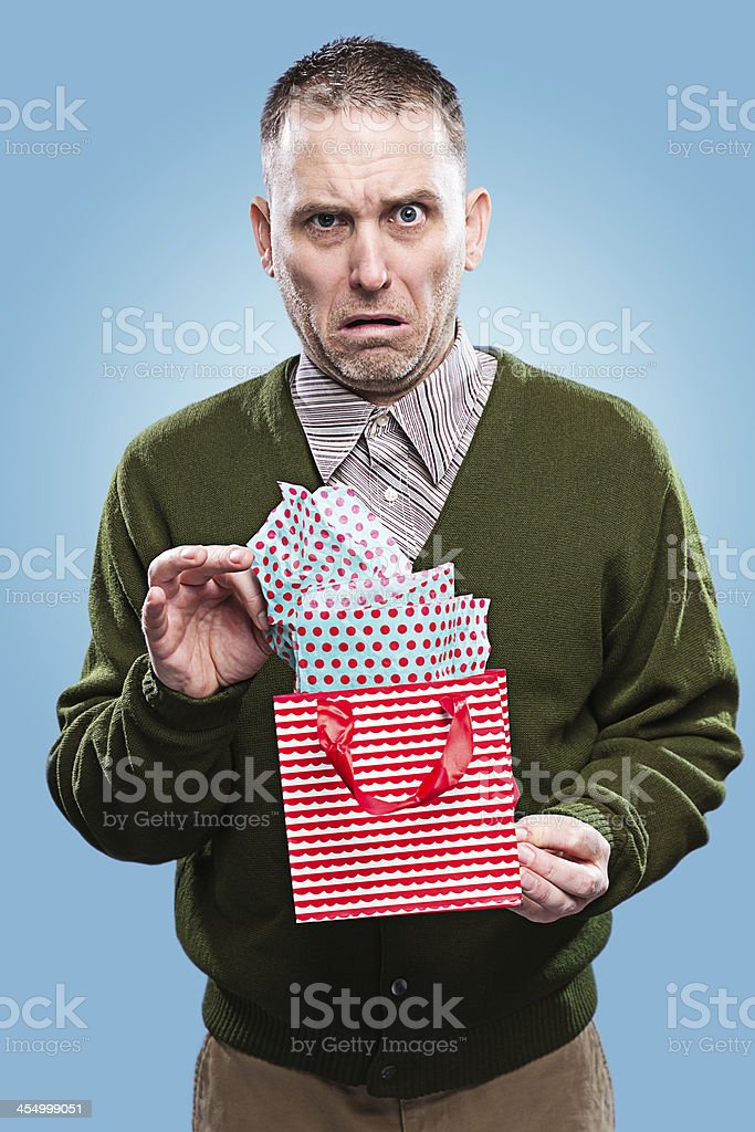 Unhappy man opening Christmas present stock photo
