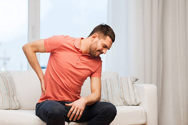 unhappy man suffering from backache at home stock photo