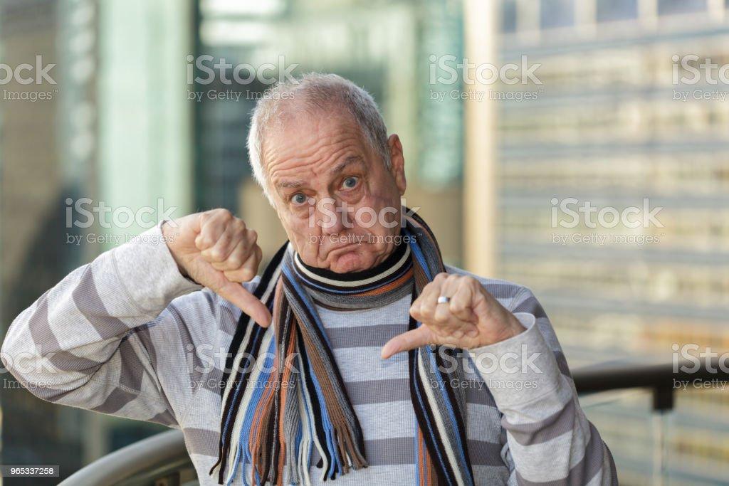 Unhappy man with facial scar, giving a thumbs down sign zbiór zdjęć royalty-free