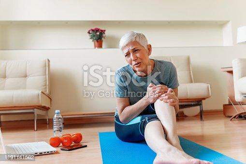 875123630 istock photo Unhappy Mature woman sitting on the mat 1191141562