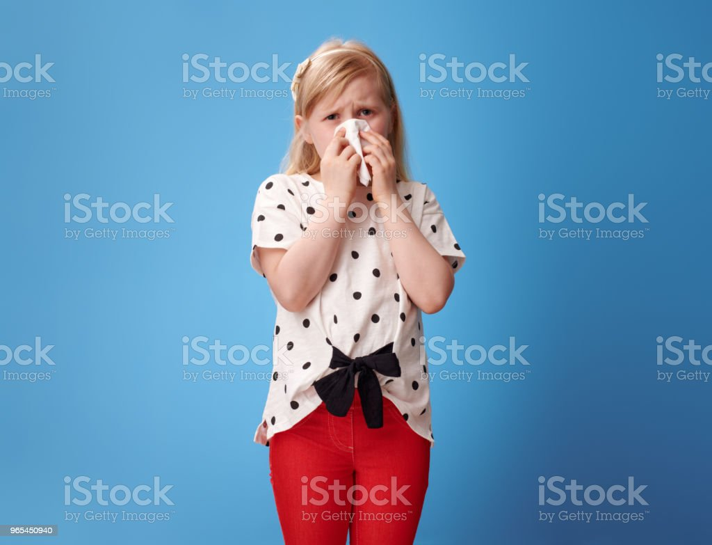 unhappy modern child in red pants on blue blowing nose zbiór zdjęć royalty-free