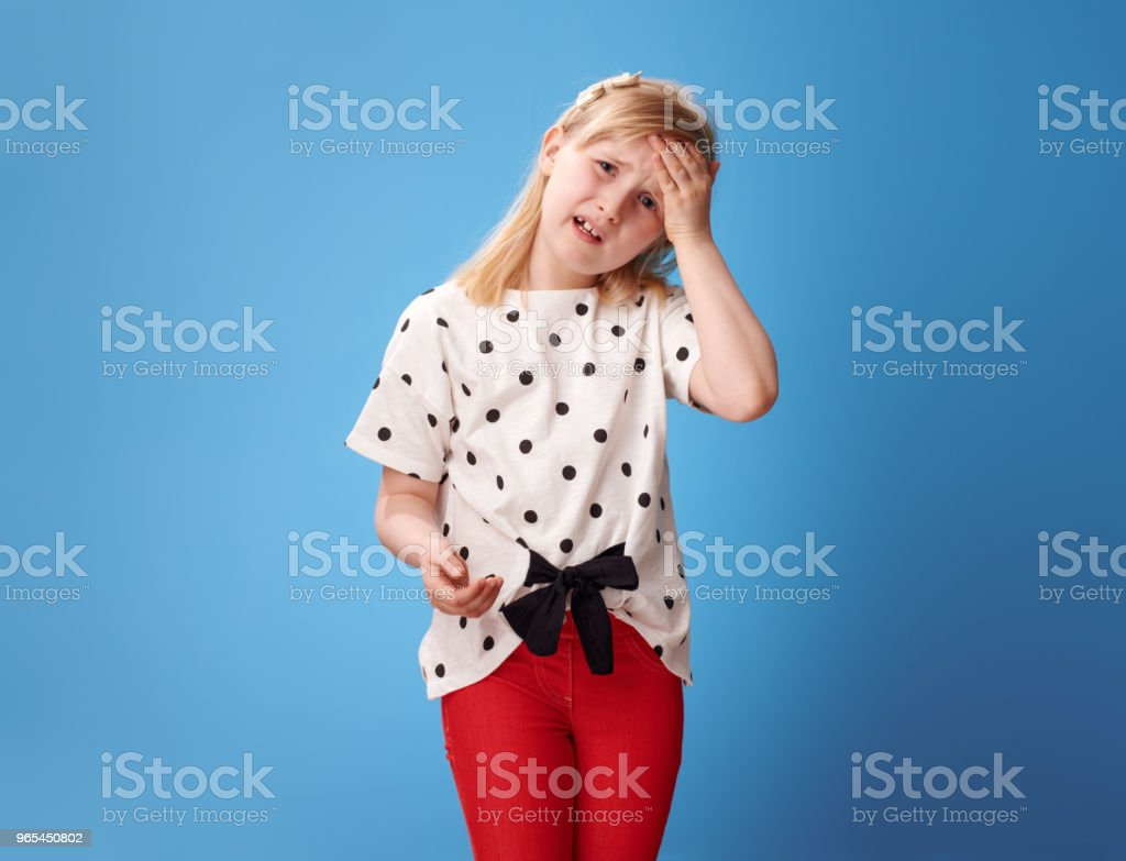 unhappy modern child in red pants on blue having headache royalty-free stock photo