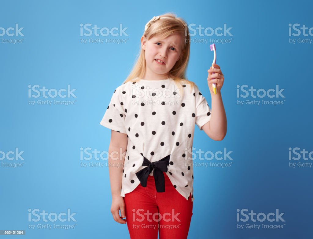 unhappy modern child in red pants on blue holding toothbrush zbiór zdjęć royalty-free