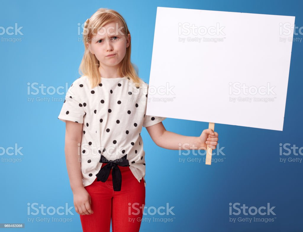 unhappy modern girl in red pants on blue showing blank poster royalty-free stock photo