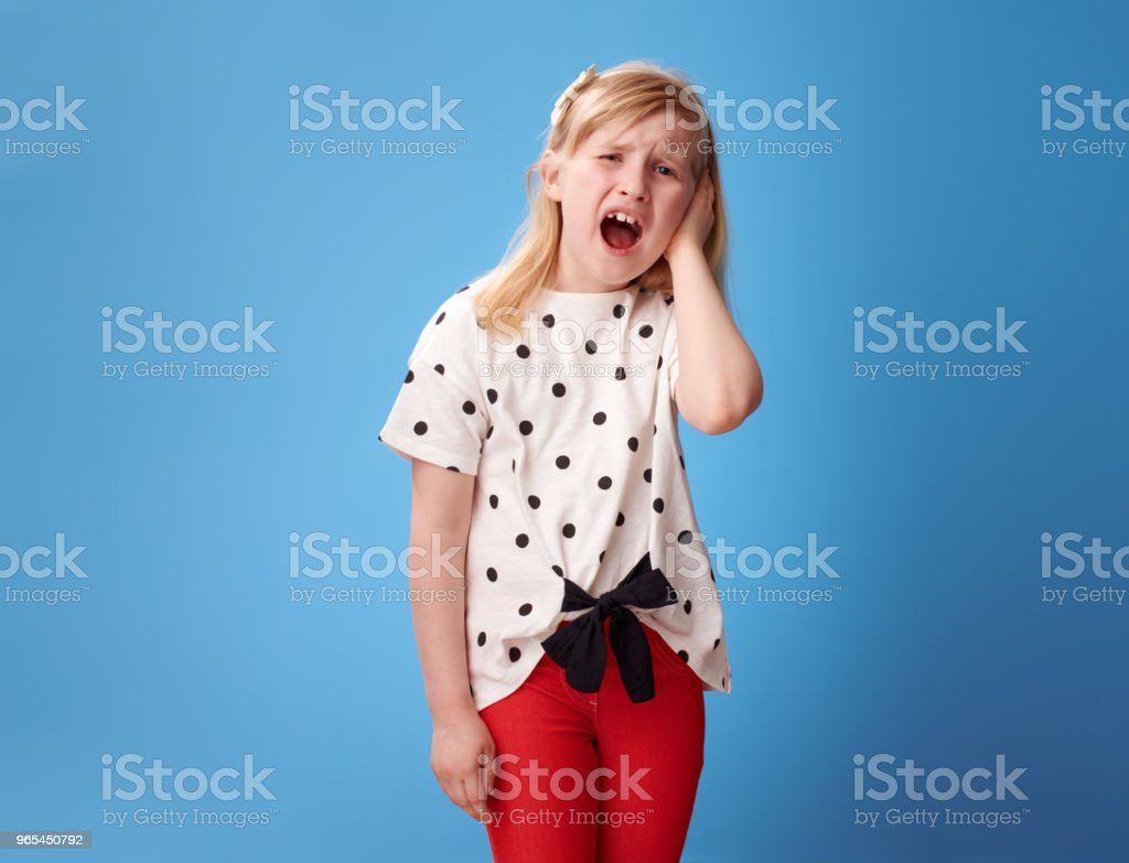 unhappy modern girl in red pants on blue with earache zbiór zdjęć royalty-free
