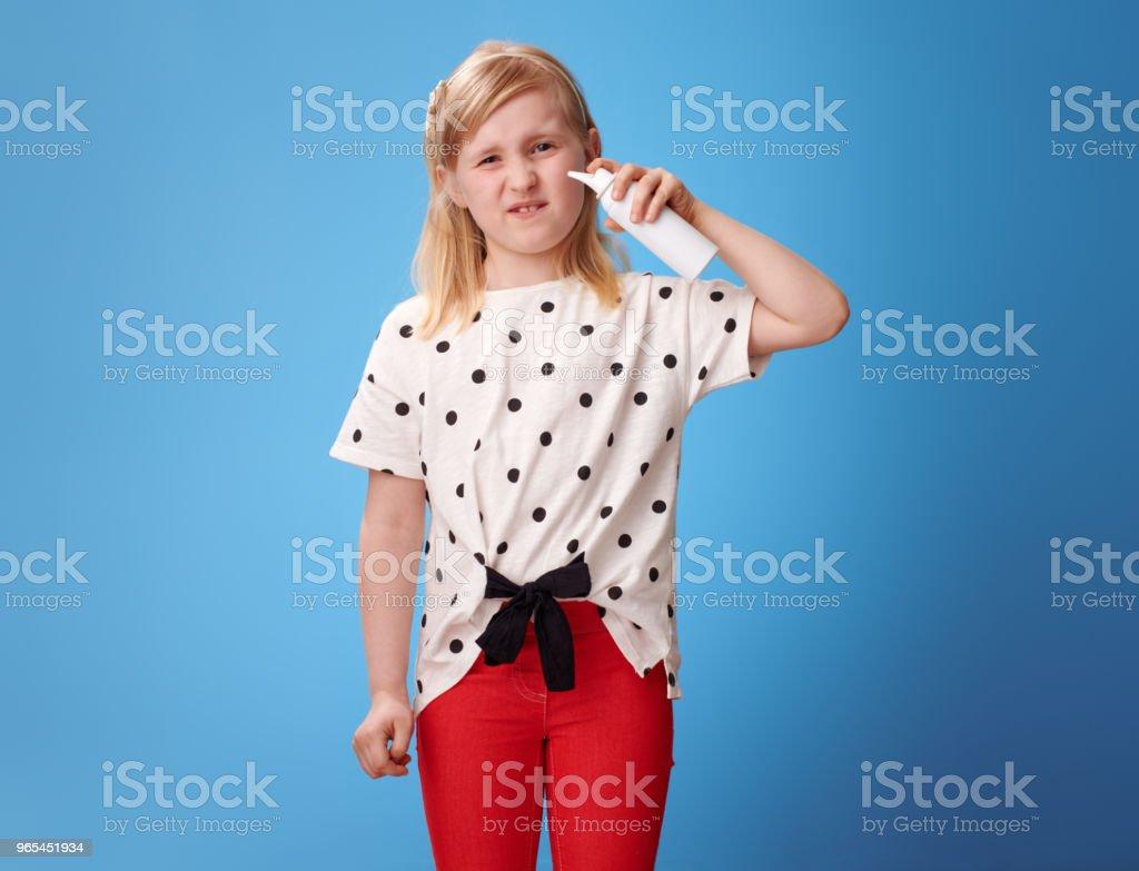 malheureuse jeune fille moderne, à l'aide de spray nasal d'eau de mer isotonique sur bleu - Photo de Alimentation lourde libre de droits