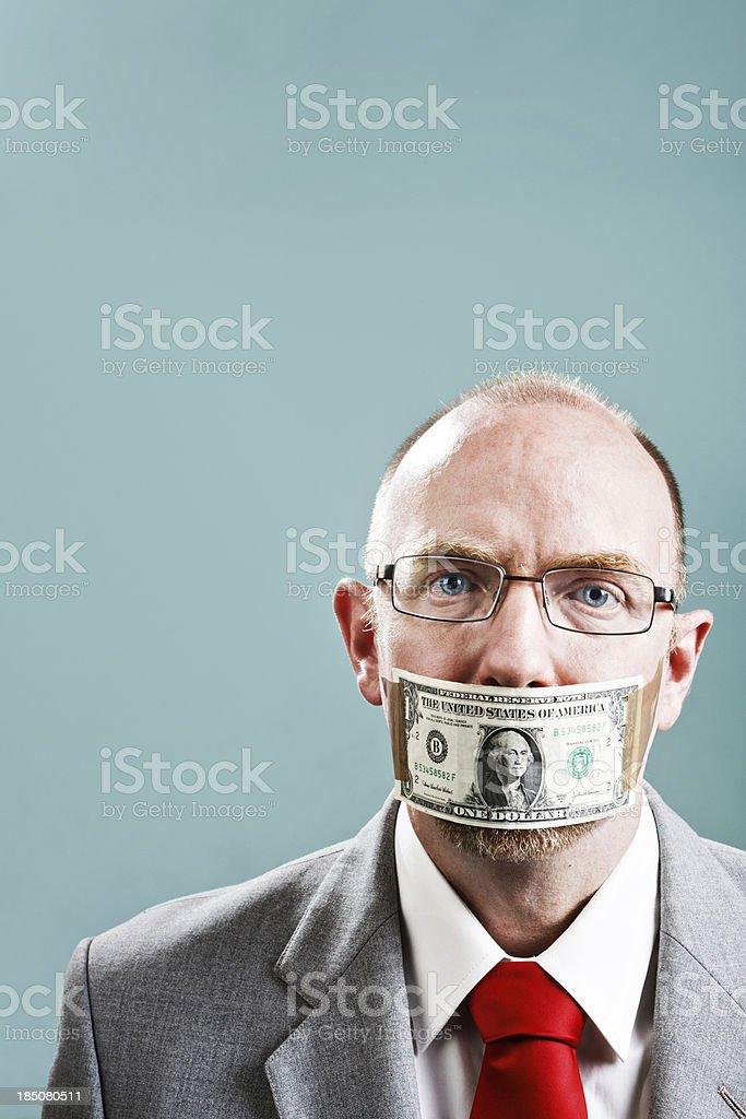 Unhappy nerdy businessman wearing dollar bill gag stock photo