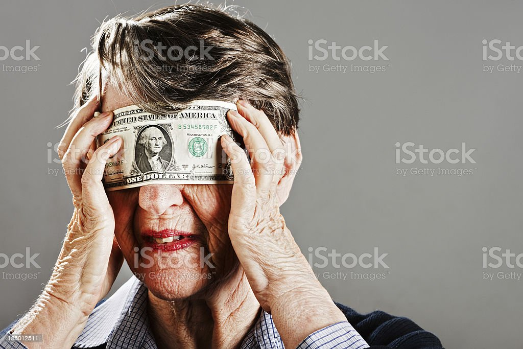 Unhappy old woman tries to remove dollar bill blindfold stock photo