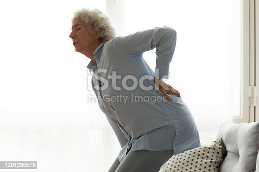 821012164 istock photo Unhappy older woman feeling pain, touching lower back 1201295578