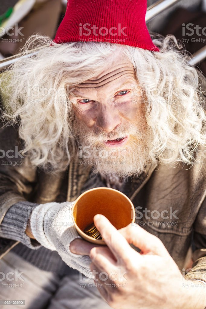 Unhappy poor man holding a cup with coins zbiór zdjęć royalty-free
