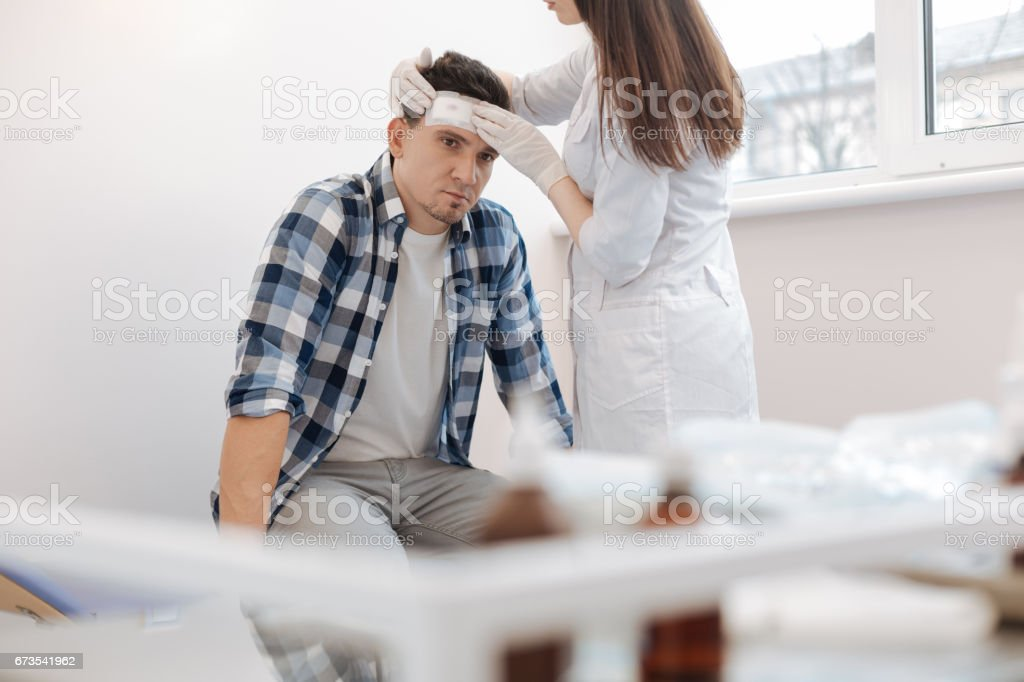 Unhappy sad man receiving the first aid stock photo
