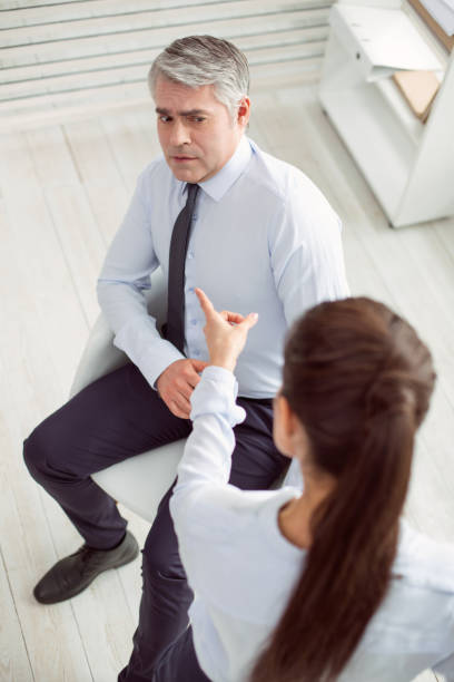 Unhappy scared man looking at his colleague Conflict at work. Nice unhappy scared man sitting on the chair and looking at his colleague while having a conflict with her prettige verrassingen stock pictures, royalty-free photos & images