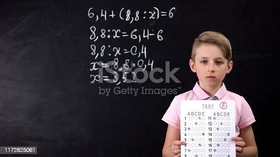 istock Unhappy schoolboy holding unsuccessful test, poor knowledge, bad education 1172825061