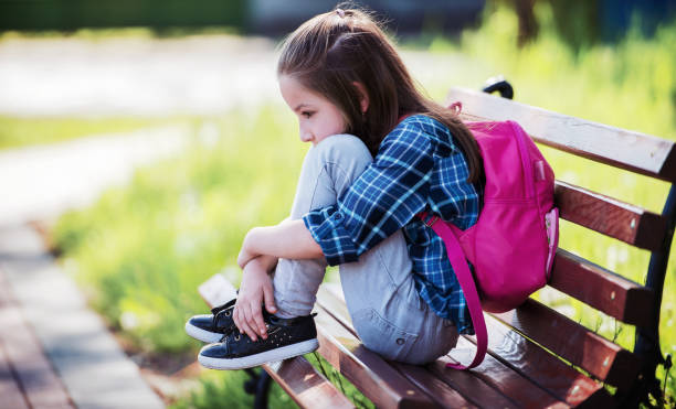 Unhappy schoolgirl sitting in the park. Education, lifestyle concept stock photo