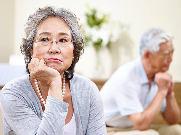 unhappy senior asian couple senior asian couple sitting on couch at home, angry at each other asian couple arguing stock pictures, royalty-free photos & images