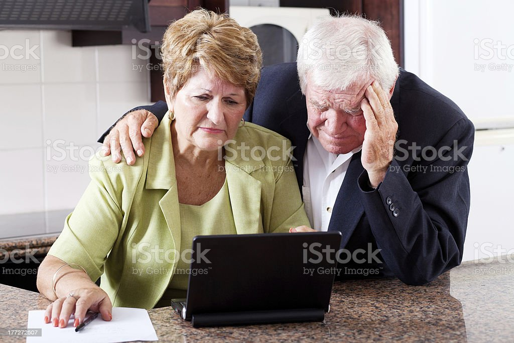 unhappy senior couple worrying about expenses stock photo