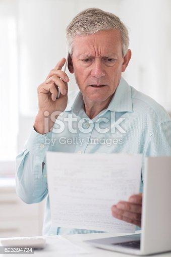 istock Unhappy Senior Man On Phone Querying Bill 823394724