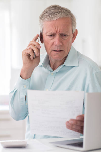 Unhappy Senior Man On Phone Querying Bill stock photo