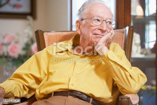 Unhappy senior man relaxing in armchair in nursing home