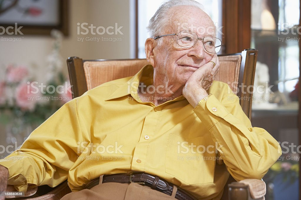 Unhappy senior man relaxing in armchair stock photo