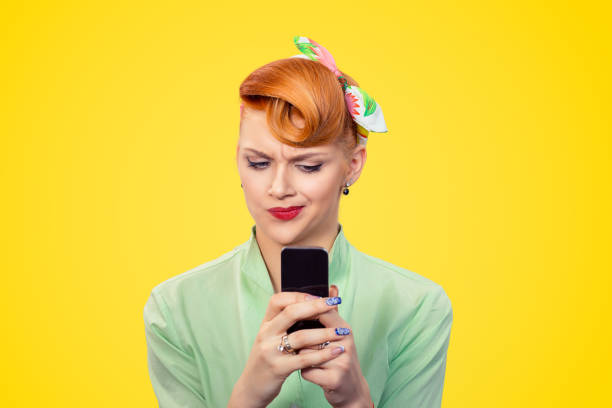 unhappy serious woman looking at texting on phone displeased with conversation - pin up girl stock pictures, royalty-free photos & images
