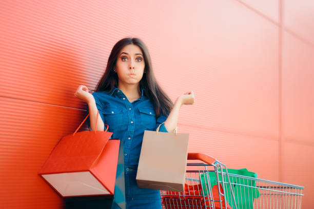 Unhappy Shopper Woman with Shopping Cart in front of Store stock photo
